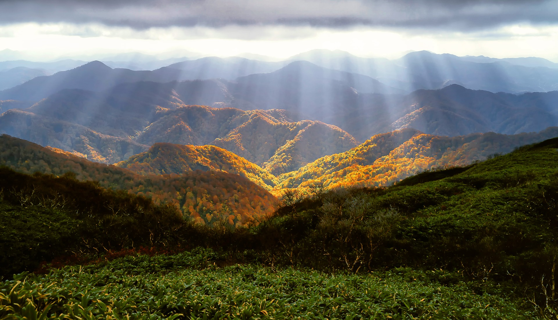 Sun breaking through the clouds in the autumn mountians