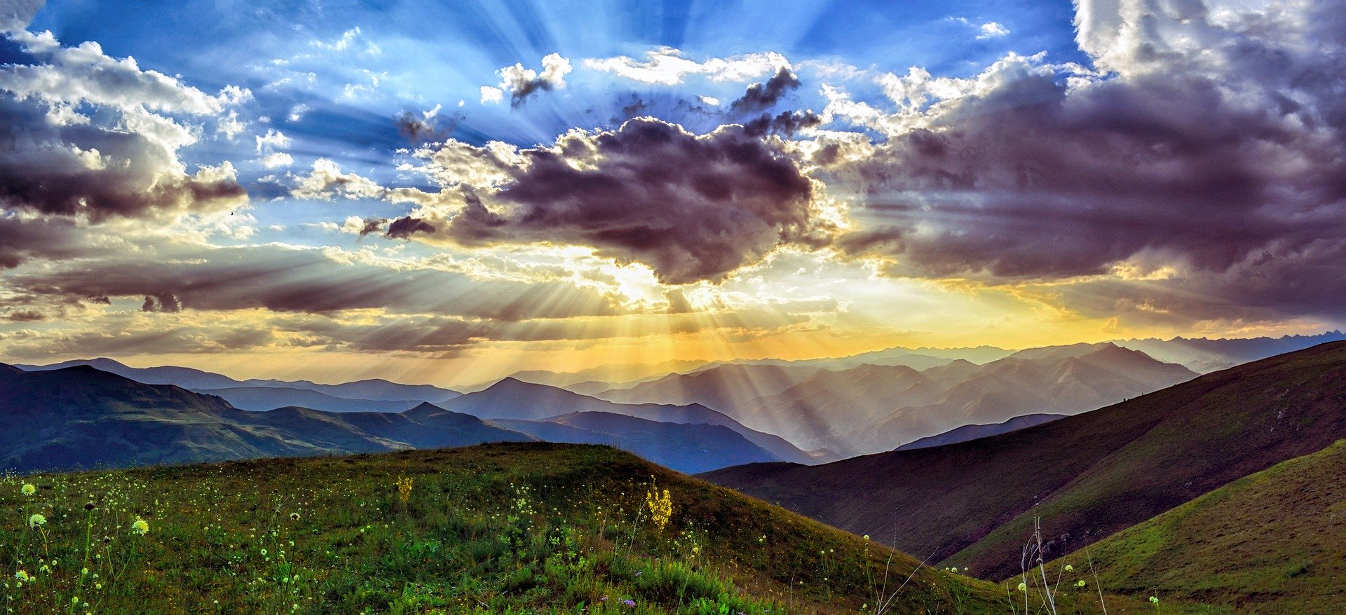 Rays of sunshine from behind a cloud over mountian range