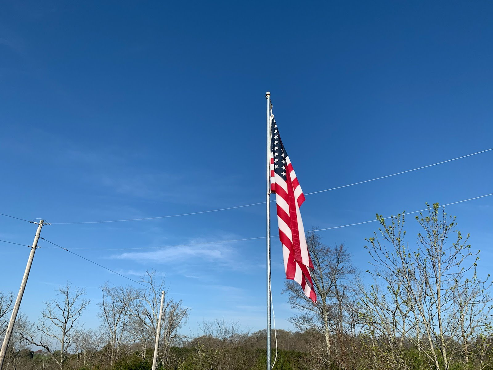 An American flag on flag post with bluse sky back drop
