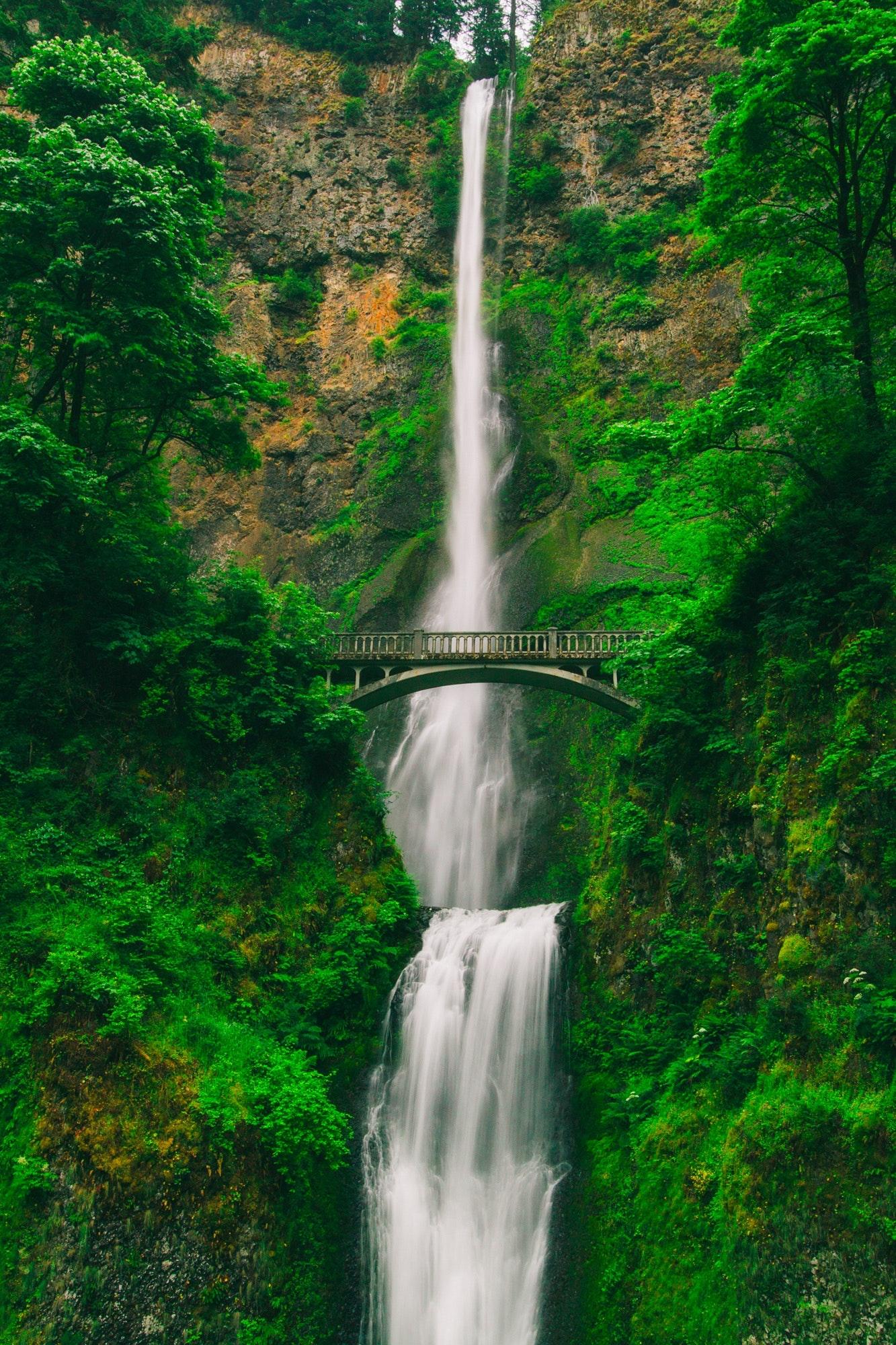 Waterfall with bridge on green cliff